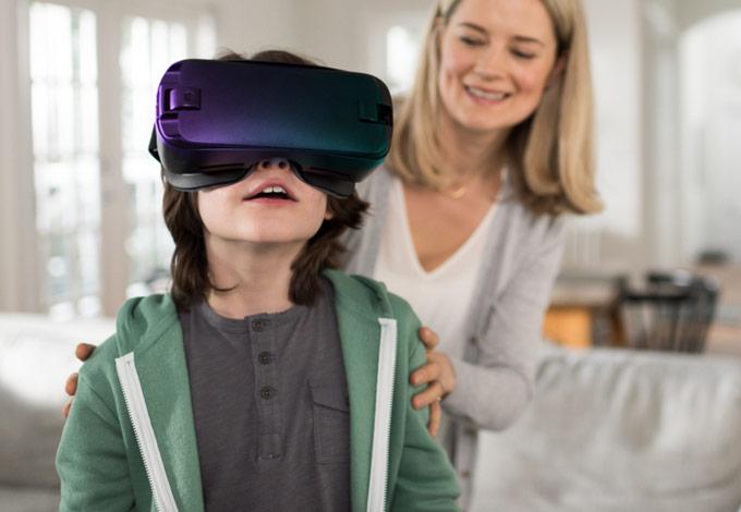 Imagen de un niño con equipo de realidad virtual y la madre detrás de él.