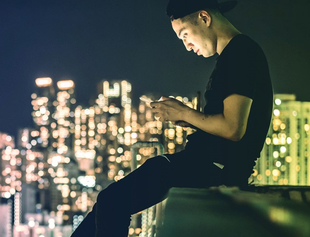 Image of a man sitting on the edge of a roof top on his phone with city skyline in the background.