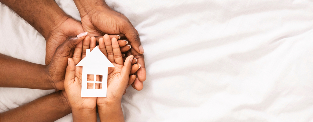 Family Holding a Small Paper Model of a House