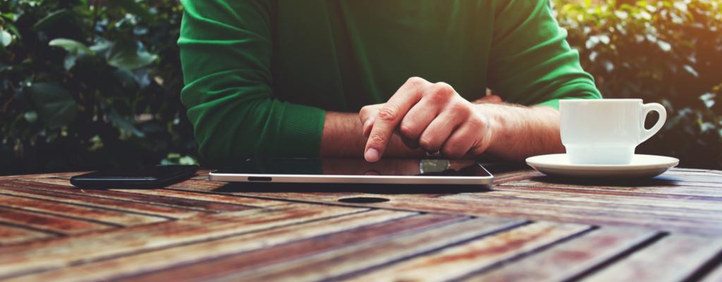 Un hombre usando una tableta en una mesa