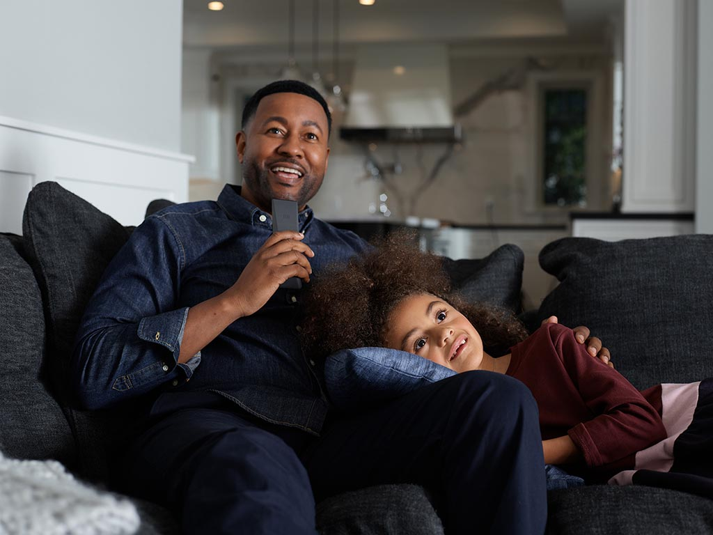 A Father and Daughter Seated on the Couch, Speaking into Their Xfinity Voice Remote