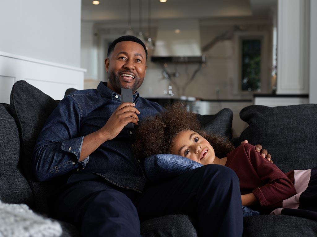 Un padre y una hija sentados en el sofá, hablando en su control remoto por voz de Xfinity