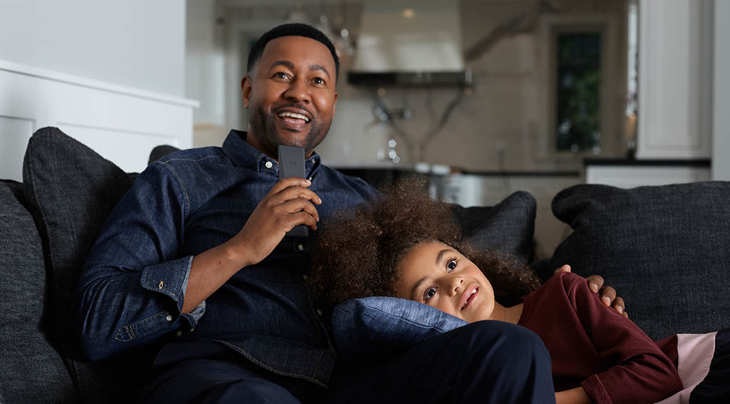 Xfinity Voice Remote Being Used by Father and Daughter in Living Room