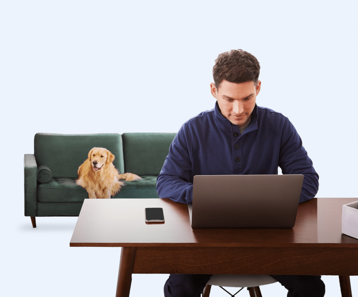 Man sitting at desk, golden retriever sitting on couch behind him