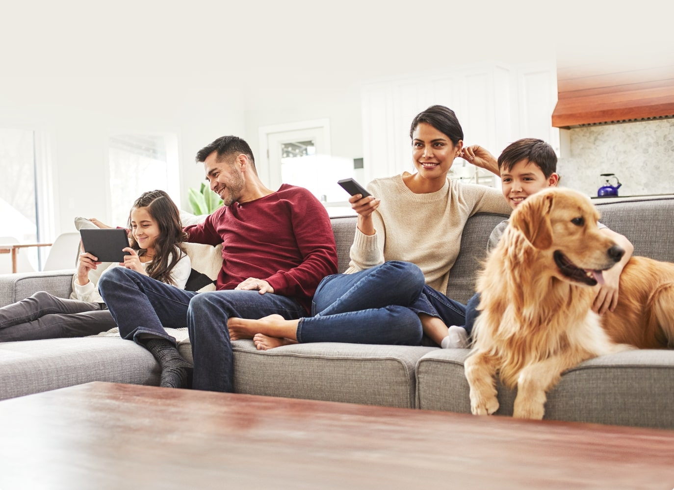 Family on couch with golden retriever