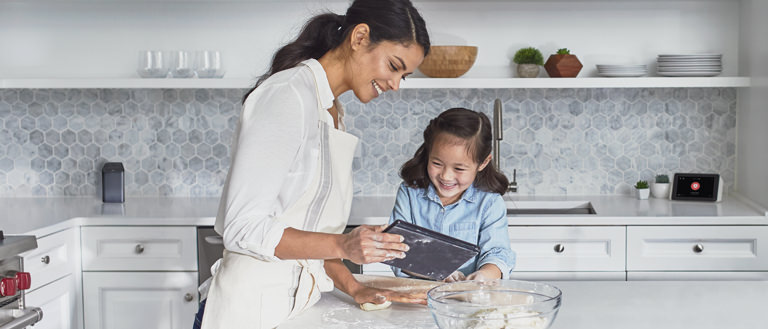 mother and daughter in kitchen looking at tablet