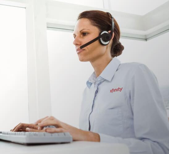 una persona con auriculares, sentada ante una computadora