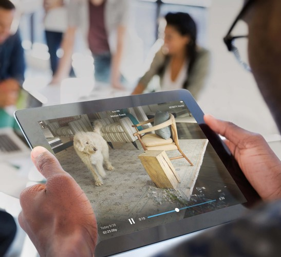 Person looking at tablet displaying Xfinity Home camera