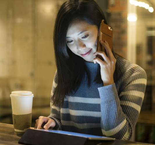 Woman looking at screen while talking on mobile device