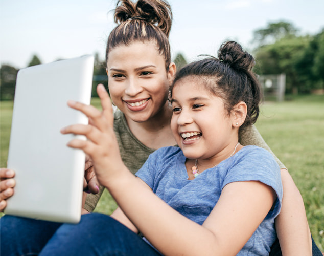 Woman and girl looking at iPad