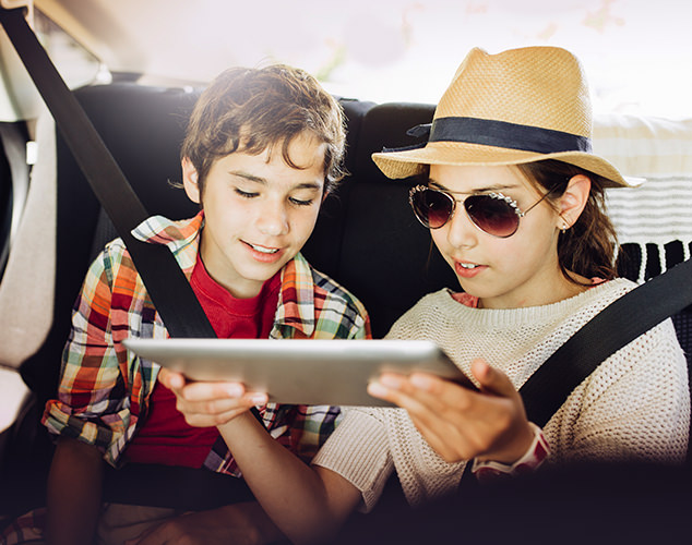 boy and girl looking at tablet in car