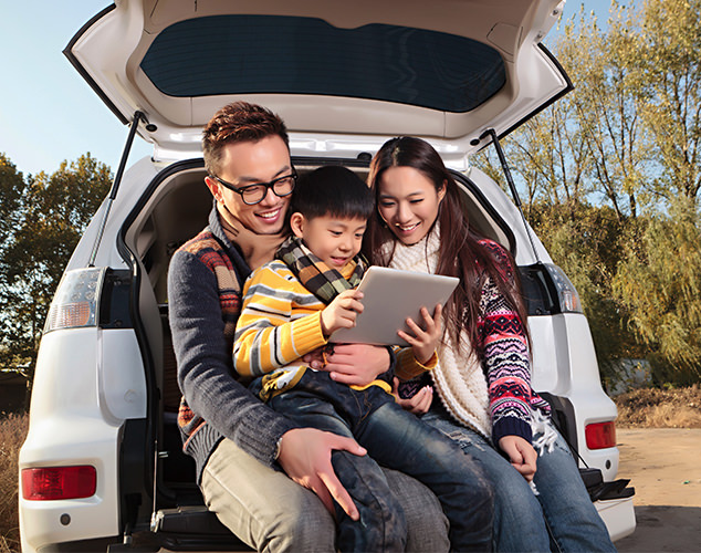 Parents and son sitting in trunk of car looking at tablet