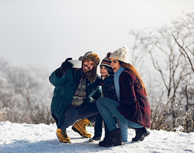 Parents and son taking selfie in snow