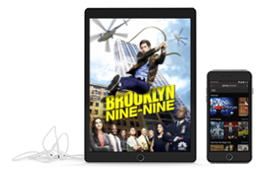 tablet showing brooklyn nine-nine next to phone and headphones