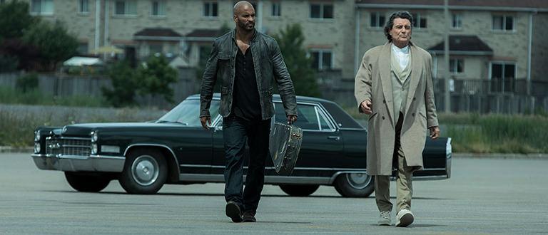 Dos hombres caminando en frente de un automóvil del show de Starz, American Gods