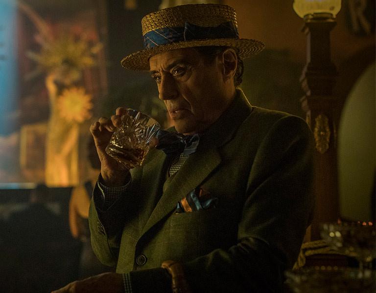 Hombre con sombrero bebiendo de un vaso con whisky
