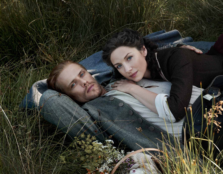 man and woman laying in grass