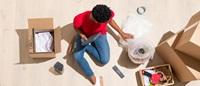 Persona sentada en el suelo con cajas de mudanza